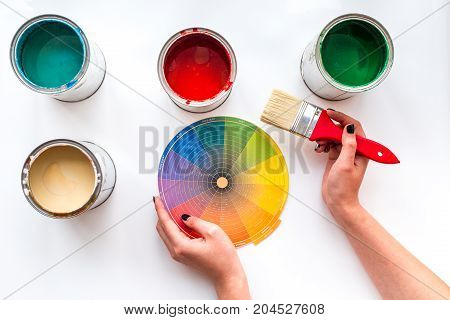Choosing color for painting. Hands hold palette and brush on white background top view.