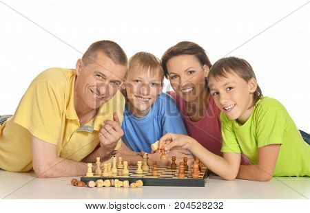 Smiling family playing chess together isolated on white background