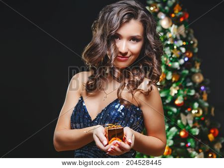 Celebrating Woman. Holiday People. Beautiful Girl with Makeup Holding Gold Present. Dark background