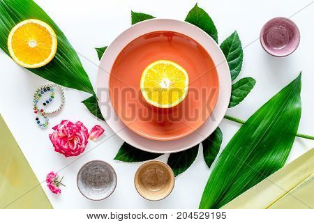 Crockery pattern. Cups and plates near tropical leaves and fruits on white background top view.
