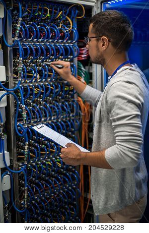 Back view portrait of young man connecting wires in server cabinet while working with supercomputer in data center