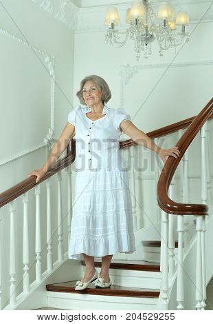 Portrait of beautiful elderly woman on stairs with railings
