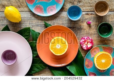 Crockery pattern. Cups and plates near tropical leaves and fruits on wooden background top view.