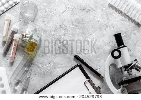 Doctor's workplace. Microscope, pills and test tube on grey stone background top view.