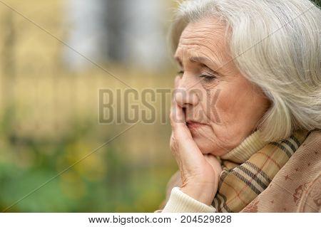 Portrait of senior beautiful sad woman posing outdoors