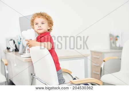 Portrait of cute little boy with blonde curly hair looking away pensively while playing at dental office