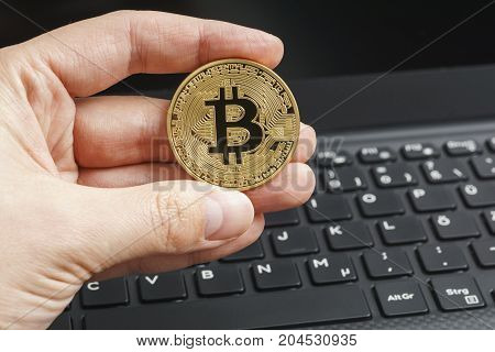 Golden bitcoin in fingers with the notebook keyboard background . Cryptocurrency concept.
