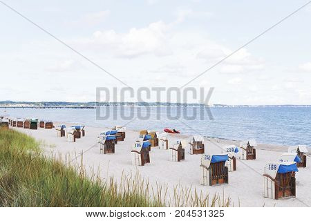 Closed Basket Chairs on a deserted autumn beach at Baltic sea.