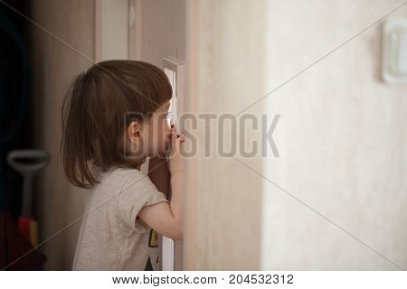 The Little Boy Looks In The Window Of The Door. A Child Spying On His Parents From Behind The Closed