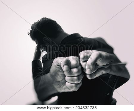 Double exposure image. Silhouette of a man in a business suit are combined with a picture of fists. Concept of confrontation competition etc. Black and white image.