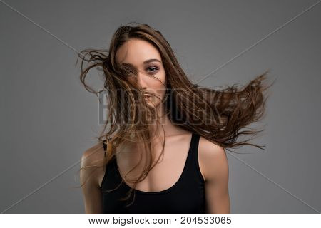 Slim pretty longhaired brunette wearing black top cropped view against gray background
