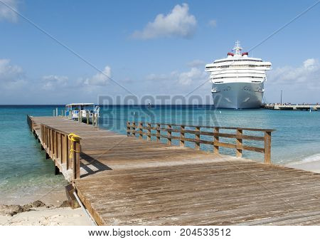 The view of a wooden pier and a cruise liner visiting Grand Turk island (Turks and Caicos Islands).
