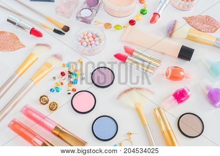 Colorful make up products flat lay scene on white background