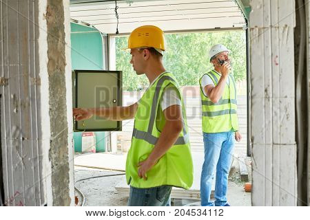 Profile view of handsome young electrician wearing hardhat and reflective jacket checking breaker box of unfinished building while his colleague talking via walkie-talkie