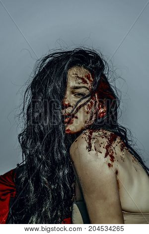 Halloween vampire with long brunette hair. Zombie posing on blue sky. Holiday celebration concept. Girl with bloody wounds on skin. Woman with red blood on naked shoulders.