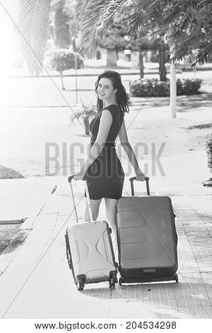 Happy girl walks and rolls two suitcases wheeled travel bags on street pavement on sunny summer day on cityscape background black and white