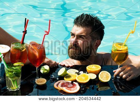 Cocktail and bearded man in pool. Drink food and relax. Leg of girl and guy with alcoholic beverage and fruit. Man swimming in water pool. Summer vacation and party.