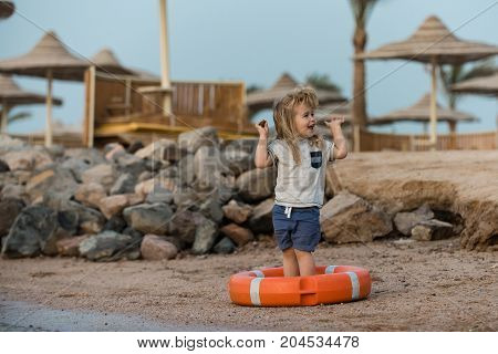 Boy child standing with hands up in life buoy. Baby care and childhood concept. Happiness and expressive emotions. Small kid laughing in orange life ring at beach. Safety on water on summer vacations.