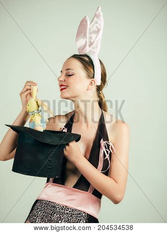 Magician pulling rabbit toy out of top hat. Girl in  lingerie on grey background. Hat trick concept. Magic and entertainment. Woman smiling in bunny ears.