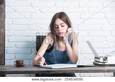 Teenager student in jean pinafore on white brick wall. Girl writing with pencil in notebook. Young woman sitting at wooden table. Study and learning concept. Education and knowledge