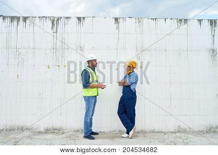 Profile view of construction inspector wearing hardhat and reflective jacket talking to young foreman and taking necessary notes on clipboard, concrete wall of unfinished building on background
