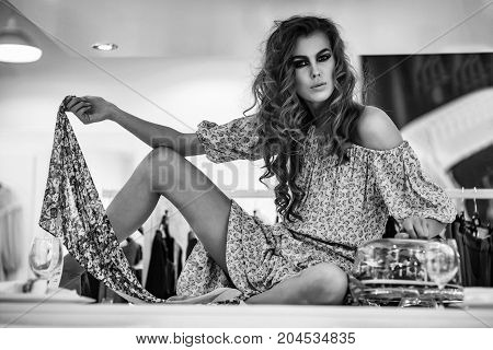 Pretty girl or beautiful woman with stylish makeup and long curly hair wearing fashionable blue dress sits on table in shop on clothing store interior background