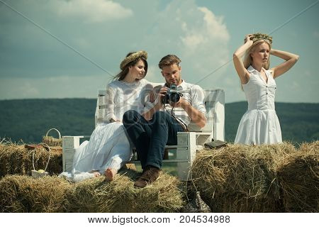 Girl and man watching photos in camera on bench. Woman in white dress putting on wreath on mountain landscape. Friends relaxing on sunny day on nature. Summer vacation concept. Lifestyle and hobby.