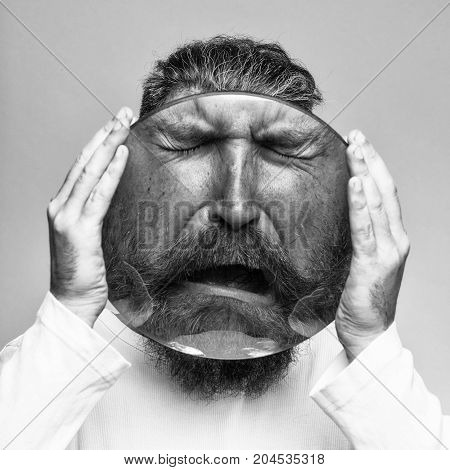 young emotional bearded man with sad crying face behind big round magnifying glass in hands as smiley on grey background