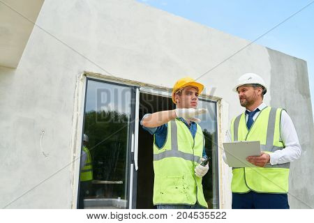 Handsome young foreman wearing hardhat and reflective jacket discussing results of accomplished work with bearded middle-aged investor, unfinished building on background