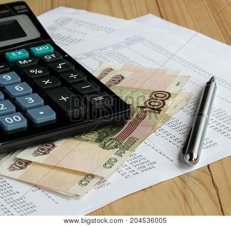 Electronic calculator metal pen and Russian money on sheets of paper with numbers. Finance Economics. Payment receipts credit calculation.