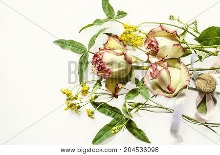 Bouquet of white with pink border roses wild flowers and clover leaves on white Bouquet of white with pink border roses wild flowers and clover leaves on white background