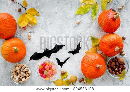 Preparing for halloween. Pumpkins and paper bats on grey background top view.