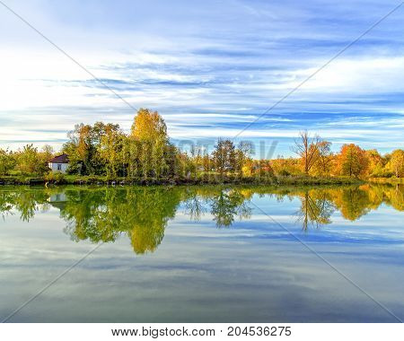 The village house on the shore of the lake is reflected in the water. Autumn forest