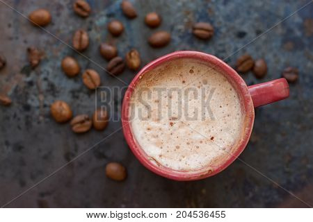 Hot coffee latte cappuccino witl milk foam in vintage ceramic cup on texture background.