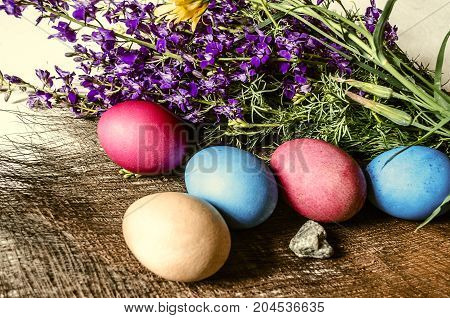 A bouquet of blooming purple wild flowers and painted Easter eggs on a straw mat
