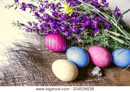 Painted Easter eggs with pebble near the bouquet of blooming purple wild flowers on a straw mat