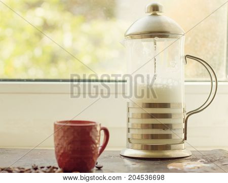 French press with whipped milk on the window
