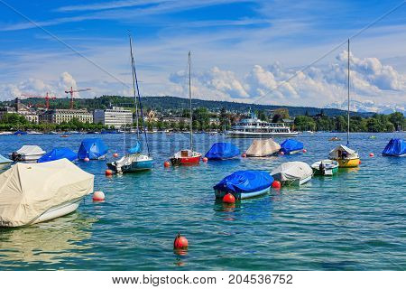 Zurich, Switzerland - 26 May, 2016: boats on Lake Zurich, buildings of the city and summits of the Alps in the background. Lake Zurich is a lake in Switzerland, extending southeast of the city of Zurich.
