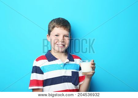Young Boy With Glass Of Milk On Blue Background
