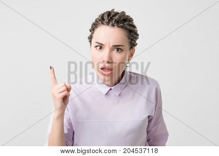 Portrait of serious, frowning, angry, grumpy young woman with african braids pointing finger upwards, scolding someone isolated on white background. People lifestyle
