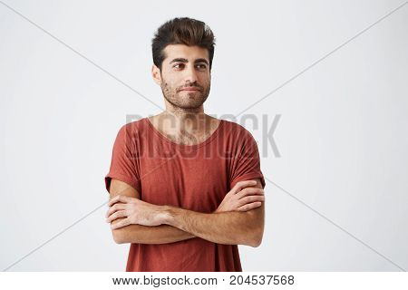 Young spanish hipster wearing red tshirt, keeping hands crossed, slightly smiling and meditative looking aside during magazine photoshoot. Beauty, people, youth and lifestyle concept.