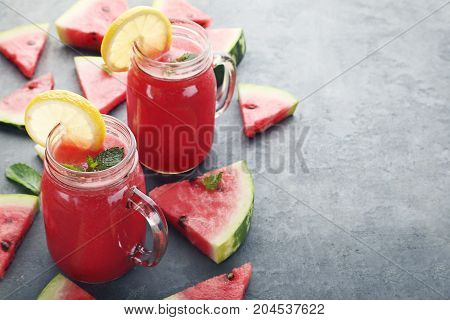 Watermelon Smoothie In Glass Jars With Sliced Fruit On Wooden Table