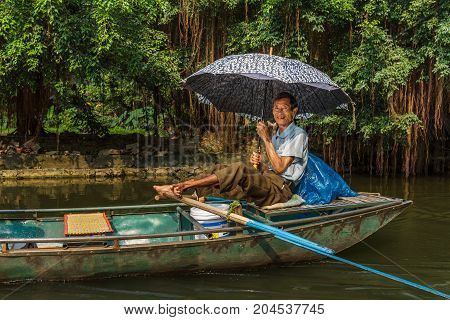 A Smiling Boat Guide At Trang An Unesco World Heritage Site In Ninh Binh, Vietnam