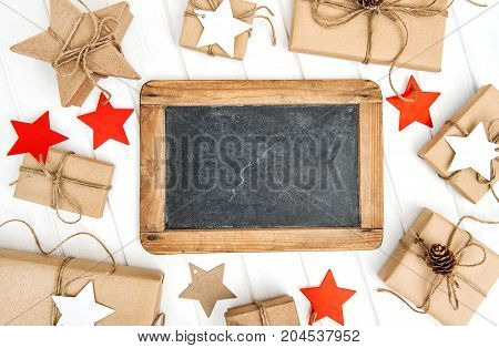 Christmas decoration with blackboard and wrapped gifts for your text