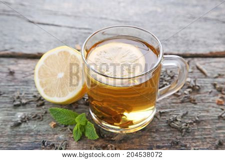 Cup Of Tea With Lemon And Mint On Wooden Table