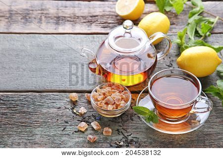 Cup Of Tea With Teapot And Sugar On Grey Wooden Table
