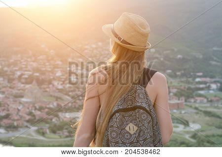 Beautiful Girl With A Backpack And In A Hat From A Height Looking At The Old City. View From The Bac