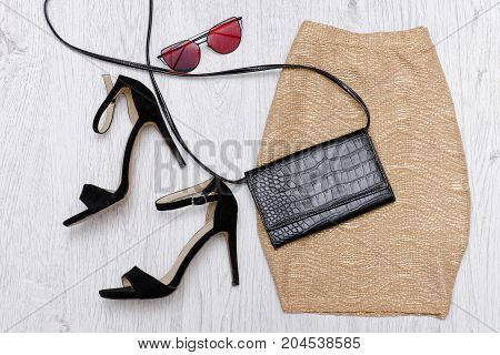 Golden Skirt, Shoes, Clutch And Glasses. Fashionable Concept. Wooden Background.