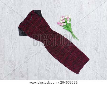 Burgundy Dress And A Bouquet Of Tulips. Fashionable Concept. Wooden Background.