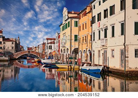 Chioggia, Venice, Italy: canal in the old town with bridge, boats and colorful reflections on the water of the ancient buildings